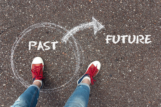 The choice between past and future. Feet  in red sneakers standing inside circle past and outward arrow on the future chalky on the asphalt.