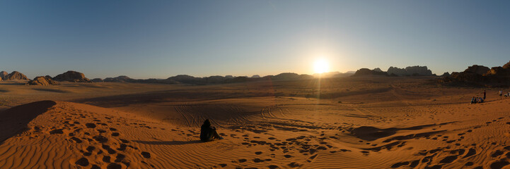 Tourists sit on a sand dune to admire sunset in Wadi Rum desert, Jordan.