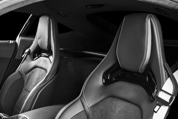 Modern Luxury sport car inside. Interior of prestige modern car. Comfortable leather seats with stitching. Black perforated leather. Modern car interior details. Car detailing. Black and white