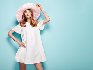Blonde Young Woman in Summer White Dress and Summer Hat. Girl Posing on a Turquoise Background. Hairstyle and Clothing. Fashion Photo