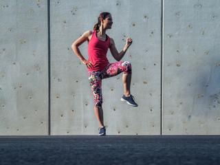 fitness lady making balance Pose outdoor infront of a grey cement wall as background