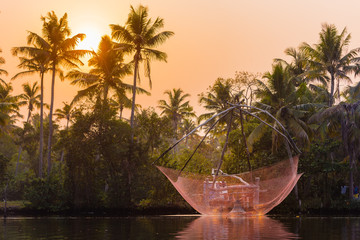 Fototapete - A traditional Chinese fishing net is raised in the sunset on a lake, Backwaters, Kerala state, India.