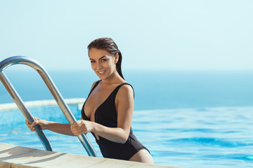 Happy young woman wearing black swimsuit on ladder getting out of infinity pool - Summer lifestyle concept with young girl enjoying time alone at resort pool.