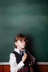 back to school. dreams and thoughts about learning, a girl in school uniform and glasses in her hand with a pencil. Student class.