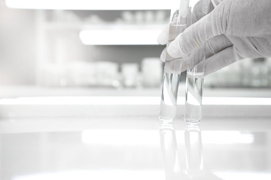 two of test tube holding by hand of scientist in medical clean white laboratory background