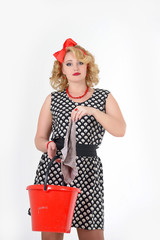 woman blonde in polka-dot dress with red bucket in hands washes floors, housewife