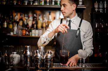 Young barman stirring fresh summer alcoholic cocktail in glass