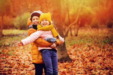 autumn portrait of happy kids playing outdoor in park. Smiling brother and sister walking in sunny day, wearing warm knitted hats and scarfs