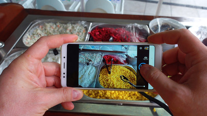 Taking photo of food with smartphone , mobile blogger. Social network concept.