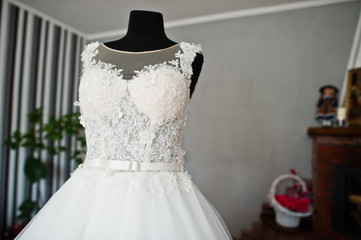 Elegant white wedding dress in the middle of the room.