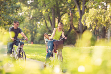 Happy father and mother with kid on bicycles having fun in park..