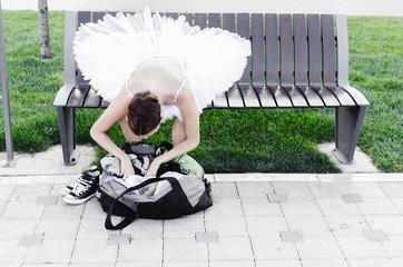 Ballerina sitting on bench in nature
