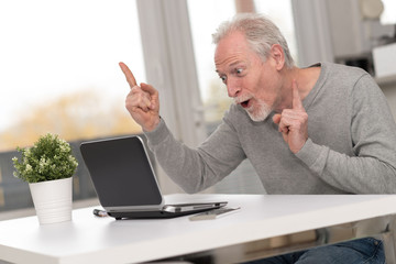 Happy mature man having a good surprise on laptop