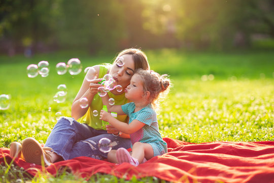 Family in park -Female child blows soup foam and make bubbles with her mother in nature.
