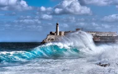 Cuba, Havana. Waves splash on the Malecon sea wall. In the background the Castillo del Morro (El Morro Fortress)