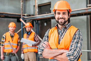 Fototapeta handsome smiling builder standing at construction site with crossed arms while his colleagues standing blurred on background obraz