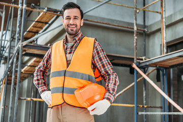 Fototapeta happy builder in reflective vest holding helmet while standing in front of building house and looking at camera obraz