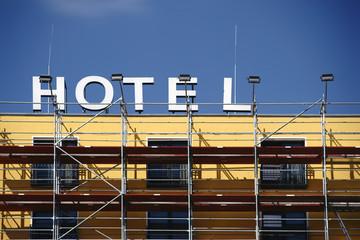 Gerüst vor der Hotelfassade / Eine Hotelfassade mit Schild wird renoviert und eine Baugerüst steht davor.