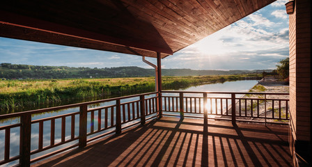 wide shot of of beautiful sunset over river from wooden terrace