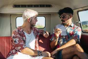 Cheerful men playing cards inside van