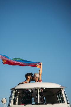 Kissing gay couple holding LGBT flag