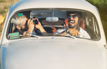 Men with camera traveling in car