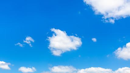fluffy clouds in dark blue sky in sunny summer day