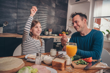 Father and daughter cracking eggs for breakfast