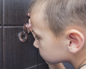 A 5 year old boy is looking at the peephole, child alone at home.