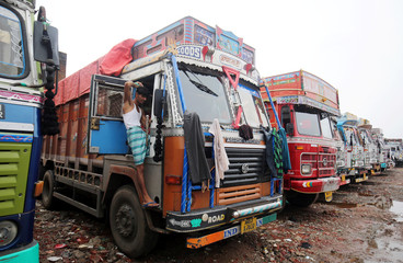 A driver combs his hair as trucks are parked inside a depot during a nationwide strike in Ahmedabad