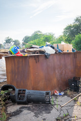 a large container with garbage stands on an asphalt road in the summer day