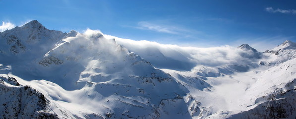 Snowy Mountains in the clouds blue sky Caucasus Elbrus