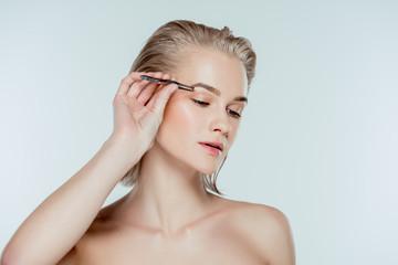 beautiful woman correcting eyebrows with tweezers, isolated on grey