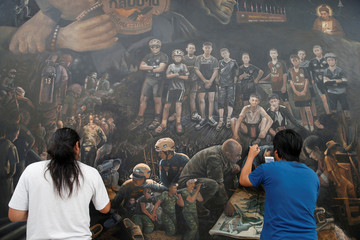 Artists paint as they work on The Heroes giant painting project, in Art Bride gallery, Chiang Rai
