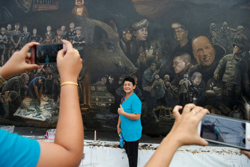 A woman poses for a photo in front of The Heroes giant painting project, in Art Bride gallery, Chiang Rai