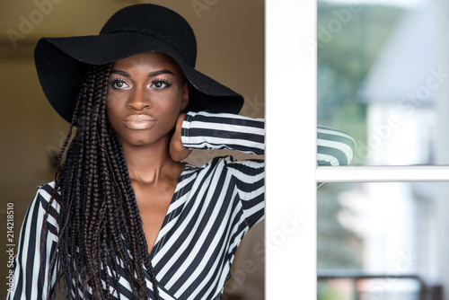Beautiful young african american girl with dreadlocks or african braids  wearing big black hat. 1a34a86c7cc7