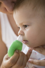 mother cleaning babies nose. vacuum pump