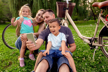 Happy family smiling while taking self - portrait in park.