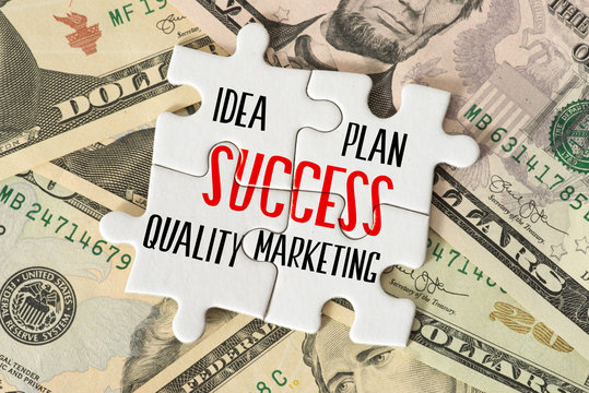 Dollar Geldscheine und Puzzleteile mit den Worten Erfolg, Idee, Plan, Qualität und Marketing