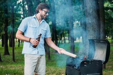 smiling man in sunglasses with beer setting fire on grill during barbecue in park