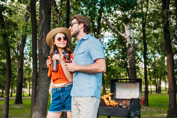 young couple in sunglasses with beer standing near grill during barbecue in park
