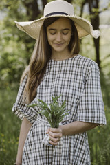 Italy, Veneto, Young woman holding bunch of tarragon