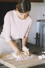 Woman preparing dough, flour and eggs