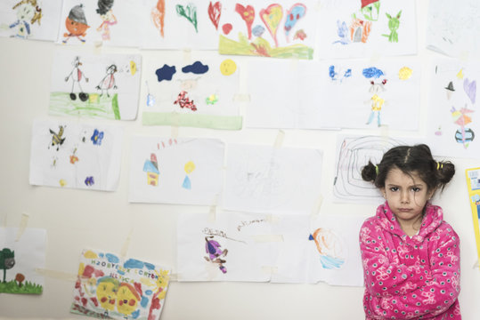 Little girl sad and angry in her bedroom with her draws in wall