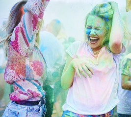 Friends dancing at music festival, holi powder