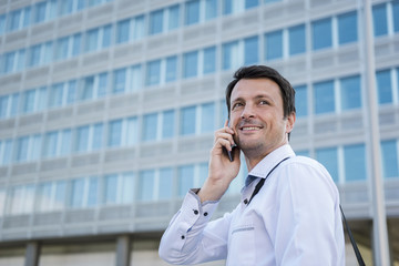 Smiling businessman on cell phone in the city