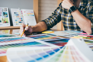 Young creative Graphic designer using graphics tablet to choosing Color swatch samples chart for selection coloring with work tools and accessories at workplace