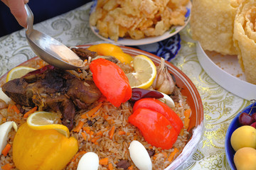 Hand with a spoon and the cup with pilaf decorated with vegetables and meat