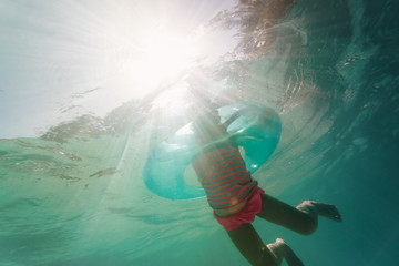 little girl swimming with floating ring underwater