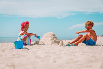little girl and boy play with sand on beach